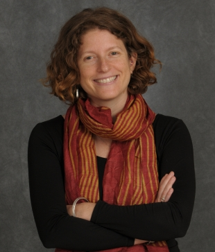 Color photo of Michele Friedner, smiling, in red and yellow scarf with arms crossed