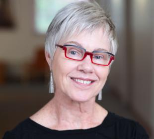 Color headshot of Rosemarie Garland-Thomson wearing black shirt, earrings, red glasses, smiling