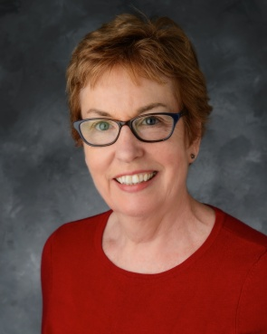 Color headshot of Mary Adamek wearing eyeglasses and red shirt