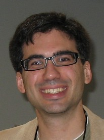 Color headshot of Juan Pablo Hourcade smiling, wearing eyeglasses and brown jacket